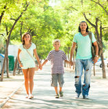 Family of three walking in summer park Stock Image