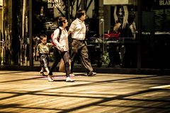 Family of three walks across Mont Blanc retail store in high end shopping stock images