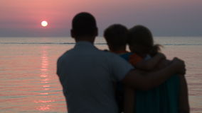 Family of three watching sunset over sea. Father holding son,they embracing mother and watching beautiful sunset over sea. Happy and close-knit family stock video