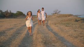 Family in white clothes walks along a dirt road stock footage