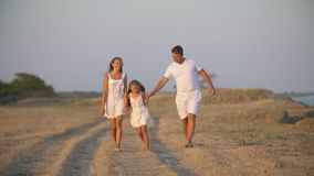 Family in white clothes walks along a dirt road stock video footage