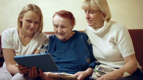 Family of three women looking photos on touchpad. Dolly shot of grandmother with her daughter and granddaughter looking photos on touchpad after looking through stock video