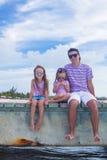Family of three on wooden dock enjoying ocean view Stock Photos