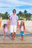 Family of three on wooden jetty by the ocean Stock Photos