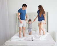 Family of three, young parents and a little son jumping and having fun in bed.  Royalty Free Stock Photography
