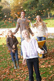 Family throwing autumn leaves into the air Royalty Free Stock Photography
