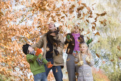 Family throwing leaves in the air Stock Photos
