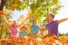 Family throwing leaves in the air during play Stock Photography