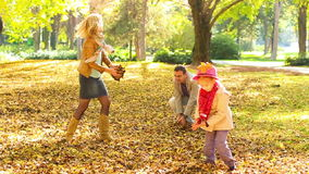 Family throwing leaves into air. Royalty Free Stock Photography