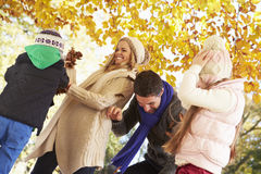 Family Throwing Leaves In Autumn Garden Stock Photos