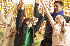 Family Throwing Leaves In Autumn Garden Stock Images