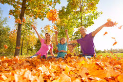 Family throwing and play with leaves while sitting Stock Photo