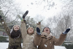 Family throwing snow into air in park Stock Images