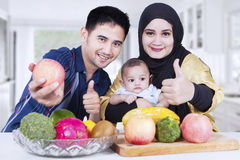 Family with thumbs-up and fruits at home Royalty Free Stock Photo