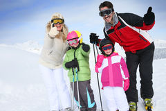 Family with thumbs up for snow holidays in a ski resort Royalty Free Stock Image