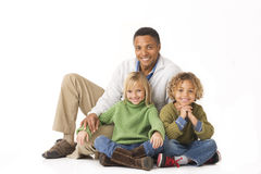 Family time. Mixed race Dad son daugher portrait sitting looking at camera on white background Royalty Free Stock Photos