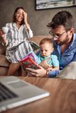 Family time- Baby boy playing with parents and together reading. Family time- Cute baby boy playing with parents and together reading a children book royalty free stock image