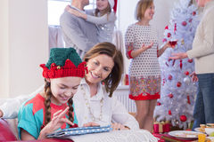 Family Time at Christmas. Three Generation Family at Christmas Time. A young girl and her grandma focus on the tablet while the rest of the family socialises in royalty free stock image