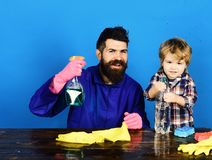 Family time concept. Kid with father holds cleaning sprays. Guy with beard and mustache and kid in checkered shirt. Man with smile and child at brown wooden stock photos