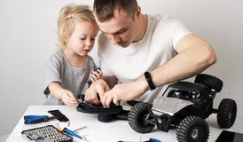 Family time: Dad and daughter repair the rc radio controlled buggy car model and lead a video blog. Portrait stock images