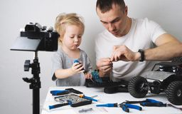 Family time: Dad and daughter repair the rc radio controlled buggy car model and lead a video blog. Portrait royalty free stock images