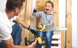Family time: Dad shows his son hand tools, a yellow screwdriver and a hacksaw. They need to drill and drill boards for. Repair. Portrait royalty free stock photography