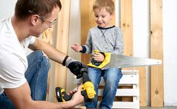 Family time: Dad shows his son hand tools, a yellow screwdriver and a hacksaw. They need to drill and drill boards for. Repair. Portrait stock images