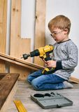 Family time: Dad shows his son hand tools, a yellow screwdriver and a hacksaw. They need to drill and drill boards for. Repair. Portrait royalty free stock photo