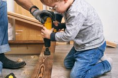 Family time: Dad shows his son hand tools, a yellow screwdriver and a hacksaw. They need to drill and drill boards for. Repair. Portrait stock image
