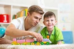 Family time. Kid boy joyfully playing building Royalty Free Stock Images