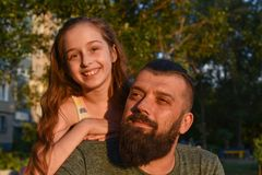 Family time. Little girl hugging her dad with a beard. Summer walk stock image