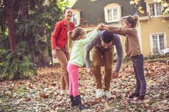 Family time little girl playing wit parents , autumn season. Leisure activity stock photography