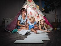 Family time: mother and children of sisters in the dark play at home in a children`s homemade tent. royalty free stock photography