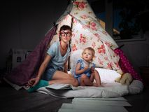 Family time: mother and children of sisters in the dark play at home in a children`s homemade tent. royalty free stock photos