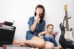 Family time: mother with son staged a home concert and sing with a microphone and an electric guitar. Candid people royalty free stock photography