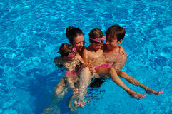 Family time in pool. Happy family of four having fun in swimming pool Stock Photos