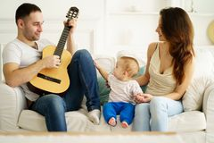 Father playing guitar for mother and son. leisure stock photography