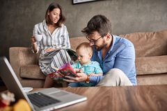 Family time- father reading book for little baby son at home. Family time- Young father reading book for little baby son at home stock photography
