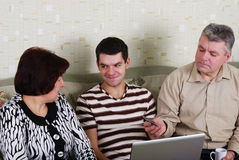 Family to view a laptop. A men and a women and a young guy on the couch with a laptop Stock Photos