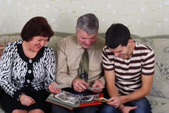 Family to view photos. Man, women and their son, watching an old photo album Stock Image