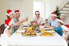 Family toasting wine while having Christmas meal Stock Photography