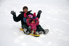 Family tobogganing. Down a hill during the winter break stock photography