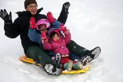 Family tobogganing. Down a hill during the winter break stock photos