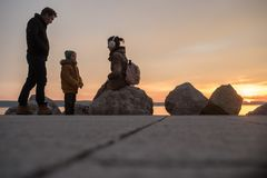 Family with toddler boy on seashore at winter sunset stock photo