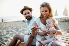 A family with a toddler girl sitting on sand beach on summer holiday. A family with a toddler girl sitting on sand beach on summer holiday, playing royalty free stock photography