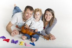 Family with a toddler is playing on the floor Stock Photos