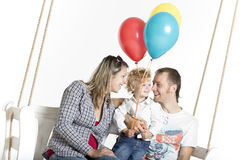 Family with a toddler is on a swing with bright balloons Royalty Free Stock Photo