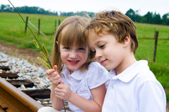 A family together. A set of boy and girl twins sitting on railroad tracks Stock Photo