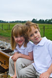 A family together. A set of boy and girl twins sitting on railroad tracks Royalty Free Stock Photography
