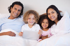 Family together on the bed with laptop Stock Photography